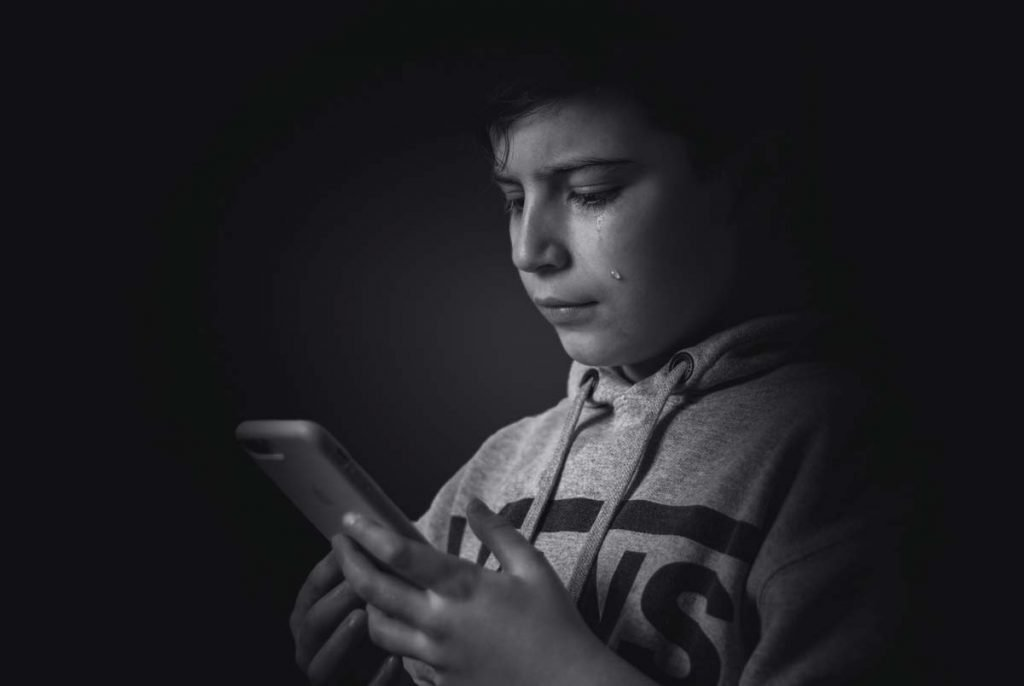 Boy using smartphone and crying - Cyberbullying